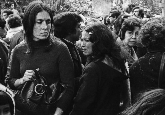 "A scene at Pablo Neruda's funeral shortly in September 1973. Marcelo Montecino, who took this photo, recalls that ""The procession came past the morgue where lists of the dead were posted on the door. As the crowd gathered at the gate of the cemetery they started to sing ""The International"" plaintively but also full of rebellion and anger."""