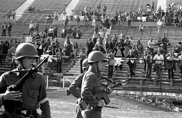 Chilean military guarding prisoners at the National Stadium after the 1973 coup. Photo by Marcelo Montecino