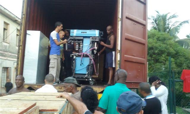 Cubans unload an anaesthesia machine from Canada